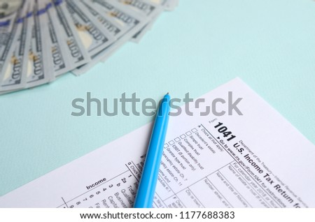1041 tax form lies near hundred dollar bills and blue pen on a light blue background. US Income tax return for estates and trusts #1177688383