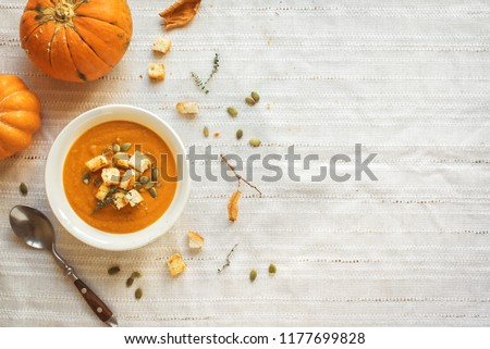 Pumpkin soup and organic pumpkins, top view, copy space. Seasonal autumn food - Spicy pumpkin soup with croutons and pumpkin seeds. #1177699828