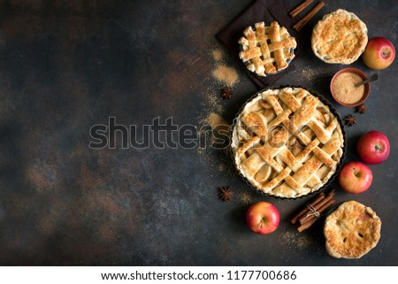 Homemade Apple Pies on rustic background, top view, copy space. Classic autumn Thanksgiving dessert - organic apple pie. #1177700686