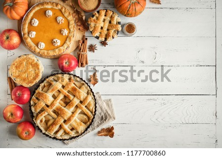Thanksgiving pumpkin and apple various pies on white, top view, copy space. Fall traditional homemade apple and pumpkin pie for autumn holiday.