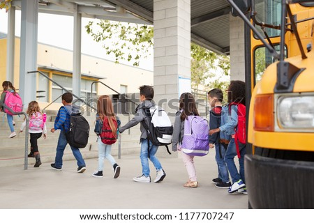 Elementary school kids arrive at school from the school bus Royalty-Free Stock Photo #1177707247