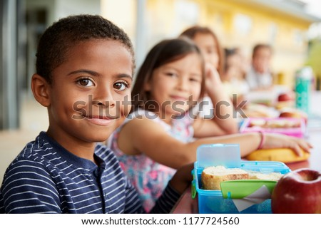 Young boy and girl at school lunch table smiling to camera #1177724560