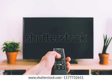 Television with remote control in hand mockup Royalty-Free Stock Photo #1177732651
