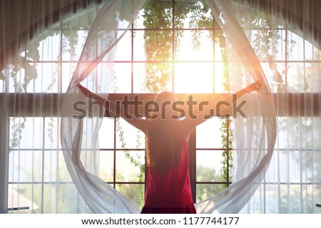Portrait of a young girl in a red dress and a yellow hat while she is opening a curtain the let the light come through the window. #1177744177