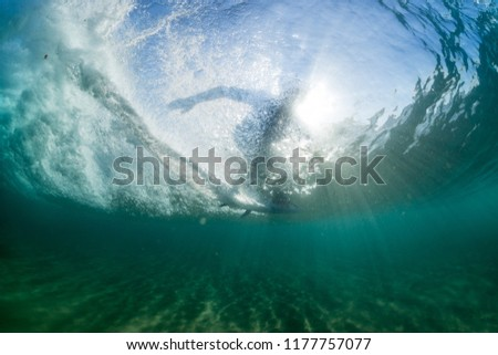 under water wave crashing, surfer, silhouette, riding, lens flare, sun rays