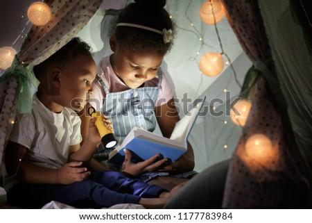 Little African-American children reading bedtime story in hovel #1177783984