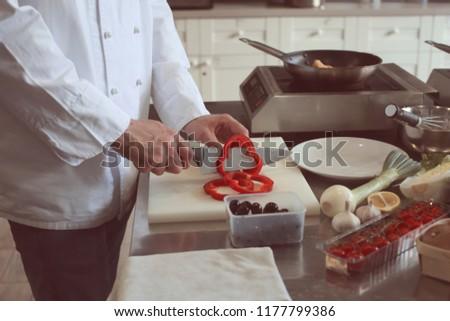 Male chef cutting vegetables in restaurant kitchen #1177799386