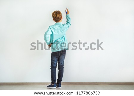 The little boy writing on the white wall #1177806739