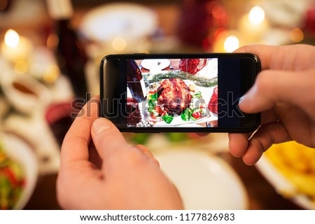 food, technology and holidays concept - close up of male hands photographing roast turkey by smartphone at christmas dinner