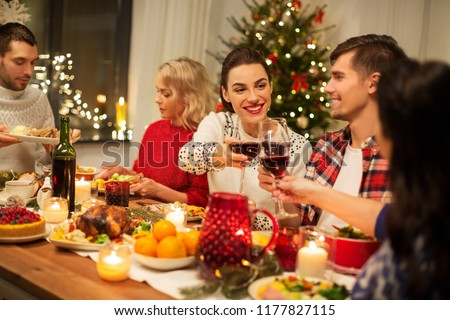 holidays and celebration concept - happy friends having christmas dinner at home, drinking red wine and clinking glasses #1177827115