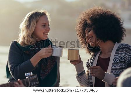 Female friends having coffee at the beach. Women with friends partying at beach and having coffee. #1177933465