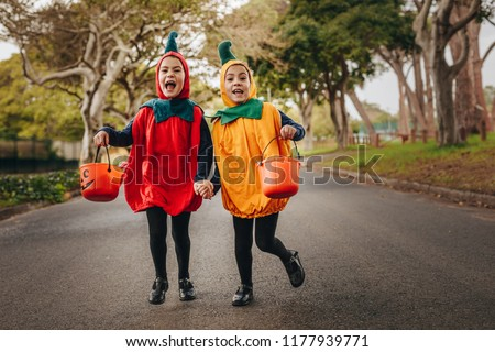 Cute little girls in halloween costume trick or treating outdoors. Identical twin sisters in halloween costume with halloween bucket walking outdoors, #1177939771