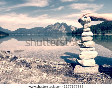 Building of stone pyramide on shore of blue water of mountain lake. Blue mountains in water level mirror #1177977883