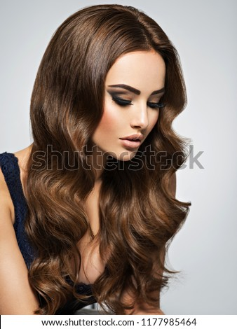 Beautiful caucasian woman with long brown curly hair. Portrait of a pretty young adult girl. Closeup face of an attractive sexy lady posing at studio over grey background. #1177985464