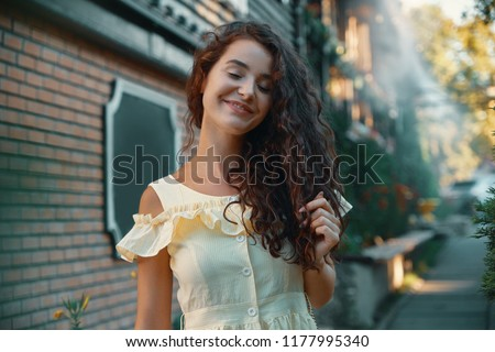 Close-up portrait of beautiful caucasian woman with charming smile walking, posing outdoors.  #1177995340