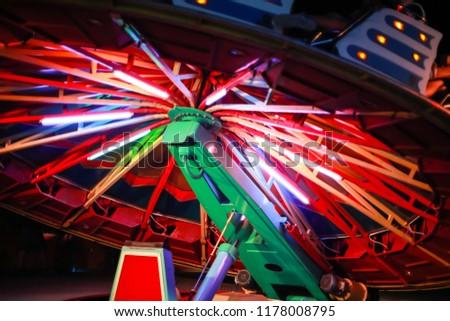 An illuminated rotating circular device in an amusement park. #1178008795