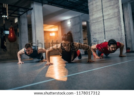 Shot of two young men and a woman standing in plank position at the gym #1178017312