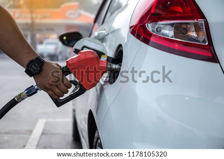Closeup of woman pumping gasoline fuel in car at gas station. Petrol or gasoline being pumped into a motor vehicle car.  Royalty-Free Stock Photo #1178105320
