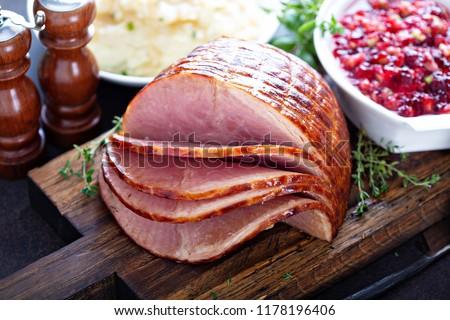 Holiday glazed sliced ham on dinner table for Thanksgiving or Christmas #1178196406