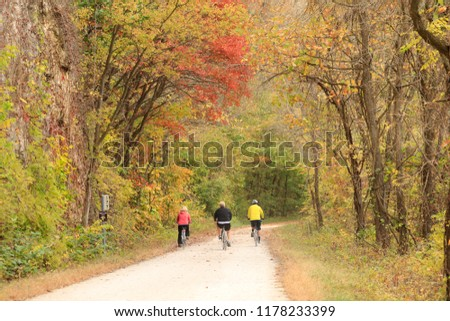 Three bicyclists riding on a trail by the bluffs in the fall #1178233399