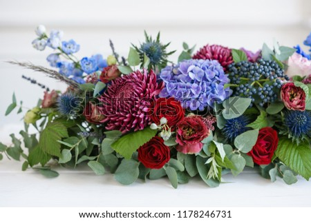Elongated floral arrangement in vintage metal vase. table setting. Blue and red color. Gorgeous bouquet of different flowers. Bright room, stucco on the wall #1178246731