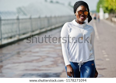 African muslim girl in sunglasses, black hijab, white sweatshirt and jeans posed outdoor against fountain. #1178271094