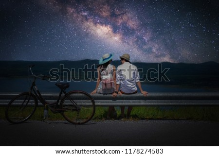 Couple traveler sitting near a bicycle and looking for the milky way and stars on the sky at night.silhouette style.this picture may have some noise.