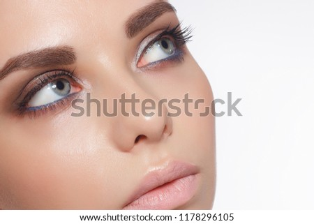 Close-up of female eyes with trendy evening make-up, thick even eyebrows and long rustnitsami. Gray-blue eyes, lenses, eyesight, cosmetology, make-up #1178296105