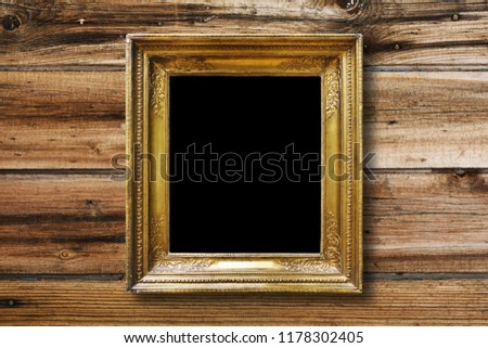 Old vintage gold ornate frame for picture on grunge wooden wall