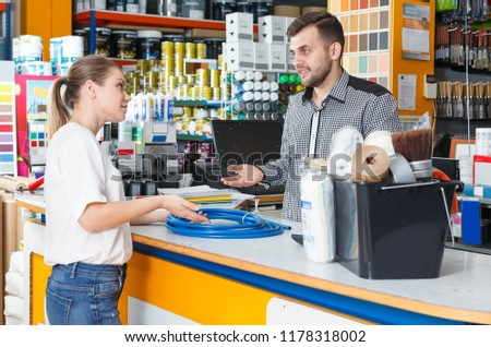 Male seller standing at the counter and discussing  with upset woman in  tools store #1178318002