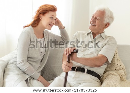 Man with a cane talking to his daughter and smiling #1178373325