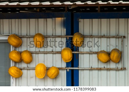 Old and worn construction helmets in yellow, black and white #1178399083