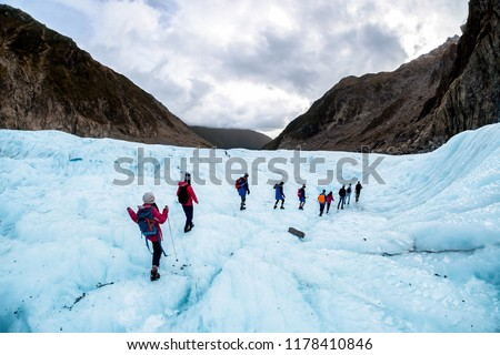 NEW ZEALAND, FOX GLACIER - MAY 2016: Hikers and travelers walking on ice in Fox Glacier, New Zealand. Breathtaking guided glacier walk onto the world-famous Fox Glacier. #1178410846