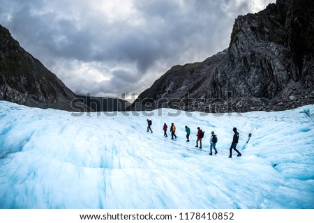 NEW ZEALAND, FOX GLACIER - MAY 2016: Hikers and travelers walking on ice in Fox Glacier, New Zealand. Breathtaking guided glacier walk onto the world-famous Fox Glacier. #1178410852