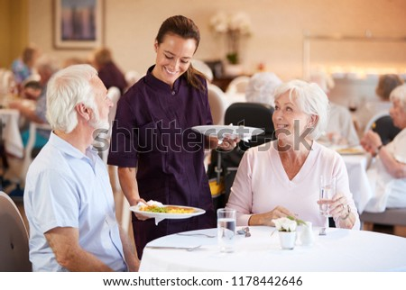 Male And Female Residents Sitting In Chair And Talking With Carer In Retirement Home #1178442646