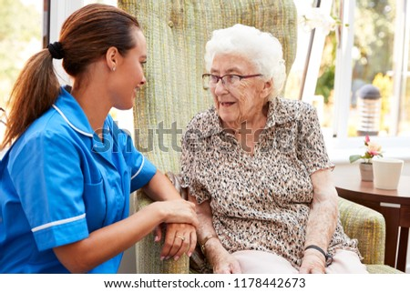 Senior Woman Sitting In Chair And Laughing With Nurse In Retirement Home #1178442673