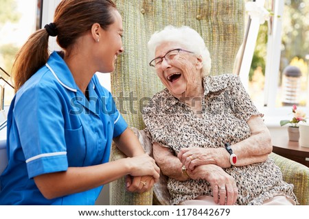 Senior Woman Sitting In Chair And Talking With Nurse In Retirement Home #1178442679