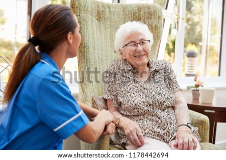 Senior Woman Sitting In Chair And Talking With Nurse In Retirement Home #1178442694