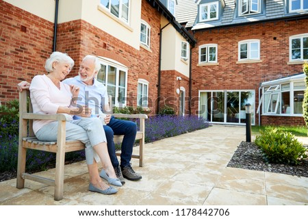 Retired Couple Sitting On Bench With Hot Drink In Assisted Living Facility Royalty-Free Stock Photo #1178442706