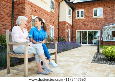 Senior Woman Sitting On Bench And Talking With Nurse In Retirement Home Royalty-Free Stock Photo #1178447563