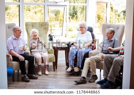 Male And Female Residents Sitting In Chairs And Talking With Carer In Lounge Of Retirement Home #1178448865