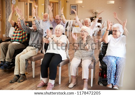 Carer Leading Group Of Seniors In Fitness Class In Retirement Home #1178472205