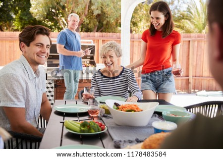 Parents and adult children having a barbecue in the garden #1178483584