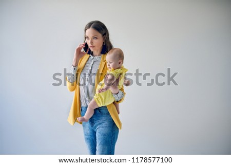 beautiful stylish mother carrying adorable infant daughter and talking by smartphone isolated on grey #1178577100