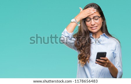 Young beautiful arab woman texting using smartphone over isolated background stressed with hand on head, shocked with shame and surprise face, angry and frustrated. Fear and upset for mistake. #1178656483