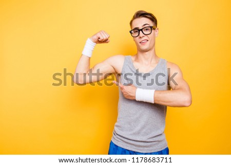 Did you see it? Portrait of funny youngster man show biceps on hand, arm isolated on bright yellow background #1178683711