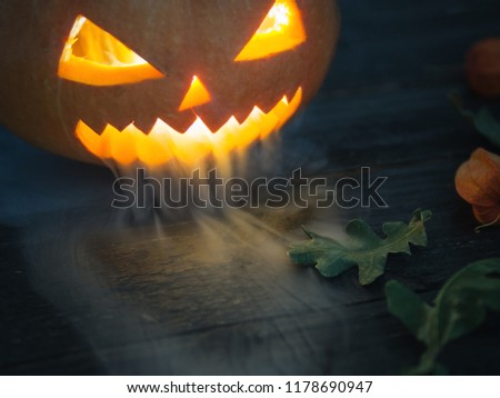 Happy Halloween and scary pumpkin exhaling smoke or steam with copy space. Deadly breath