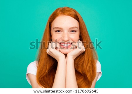 Portrait of nice calm positive cheerful cute bright vivid shiny red straight-haired girl in casual white t-shirt, holding chin with fists, isolated over turquoise green background #1178692645