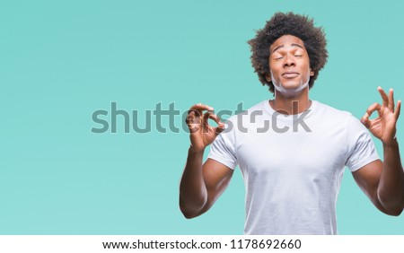 Afro american man over isolated background relax and smiling with eyes closed doing meditation gesture with fingers. Yoga concept. #1178692660
