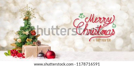 Red Merry Christmas and happy new year handwriting with xmas tree and gift box at blur bokeh light background,Winter holiday banner greeting card #1178716591